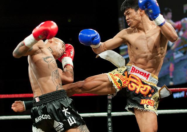 Luchador conectando una patada al cuerpo de su oponente, determinante en la puntuación.