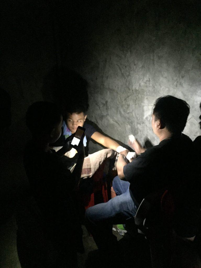 Chuy recibiendo un vendaje en sus manos a la luz de la linterna