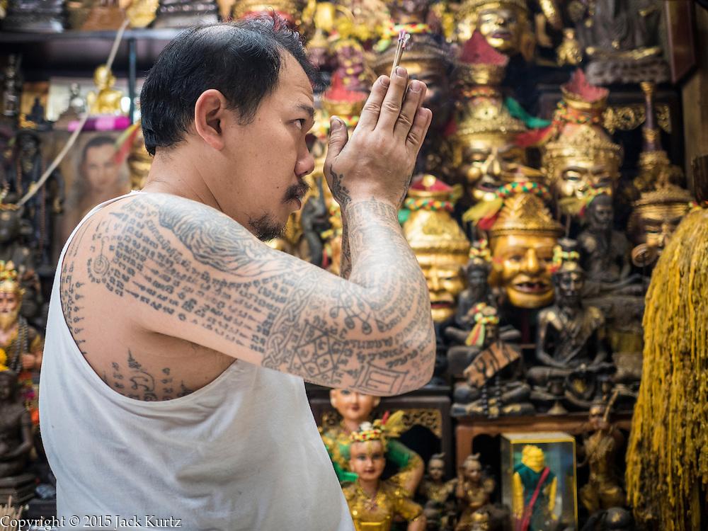 Maestro de los tatuajes realizando una oración
