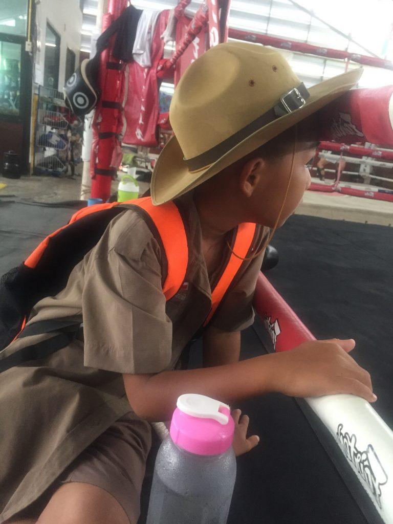 Niño con el uniforme del colegio esperando sentado en el ring