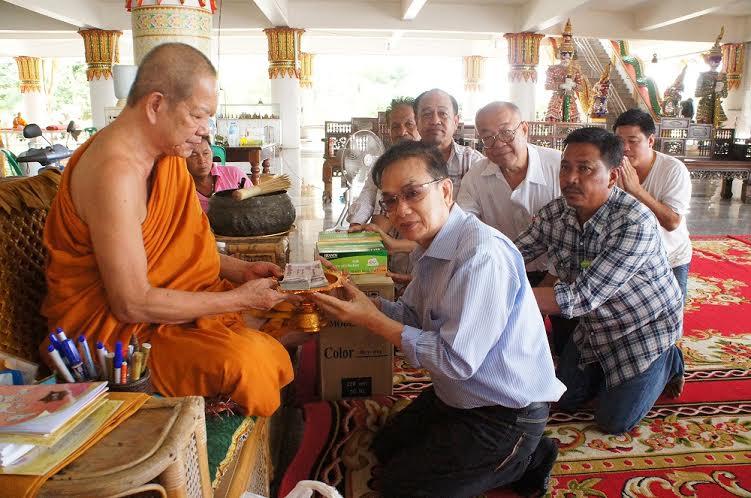 Songchai haciendo una donación a un monje